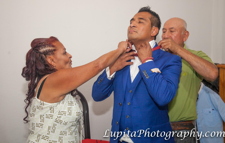 Estado de México, México - Madre y padre ayudando al novio a arreglarse para celebrar su día especial. Mother and father of the groom helping him to get ready for his special day.